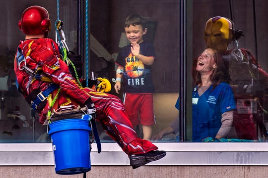 Joe Haist, from left, shares a moment dressed as Iron Man with Brennen Wilkerson, 6, as the young boy and volunteer nurse Beanie Geoghegan look on as Pro Clean International cleaned windows at Norton Children's Hospital dressed as super heroes. Feb. 21, 2019