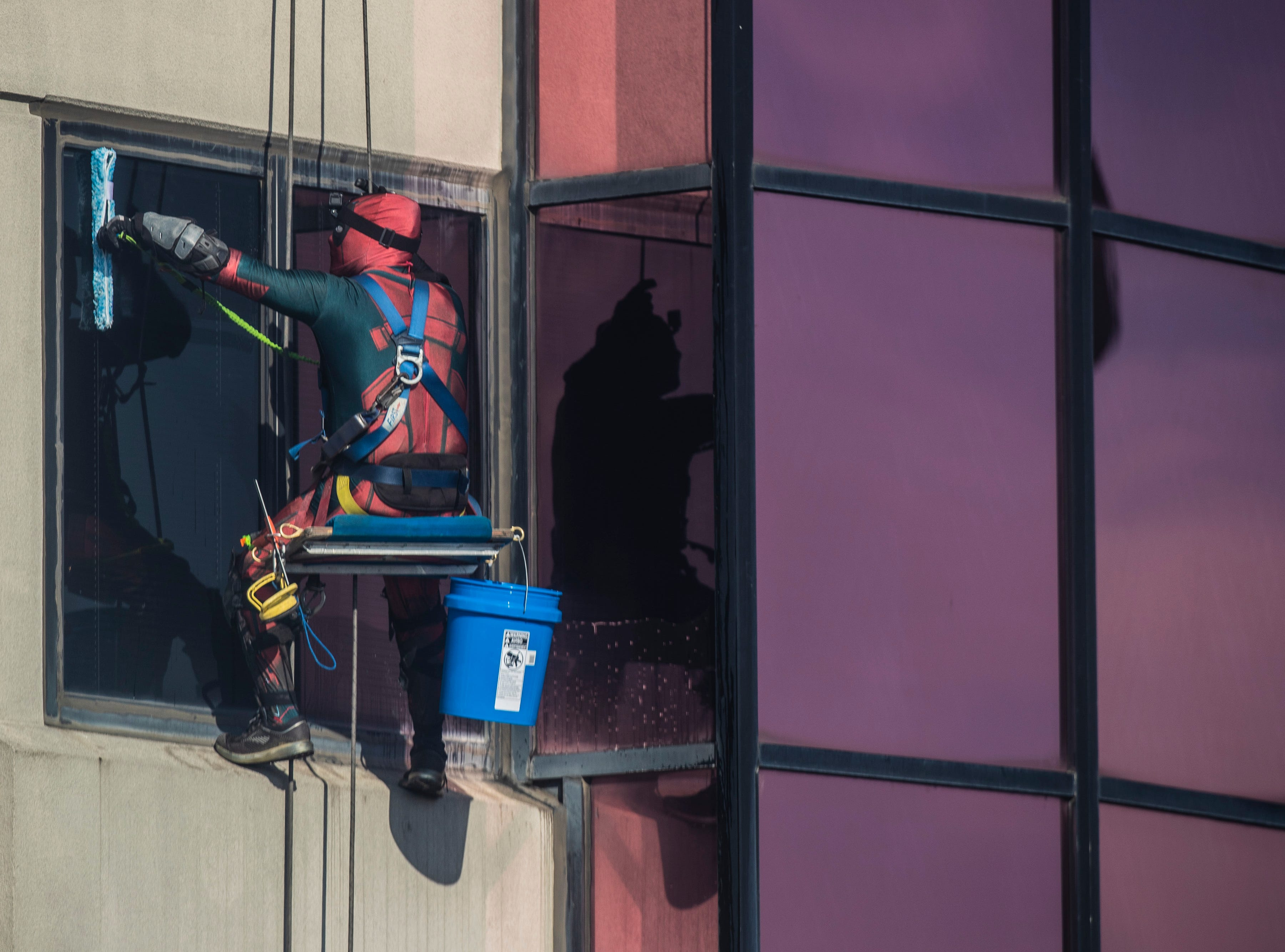 Johnny Haist with Pro Clean International is dressed as Deadpool as the window crew wore super hero costumes while cleaning the windows at Norton Children's Hospital on Thursday. Feb. 21, 2019