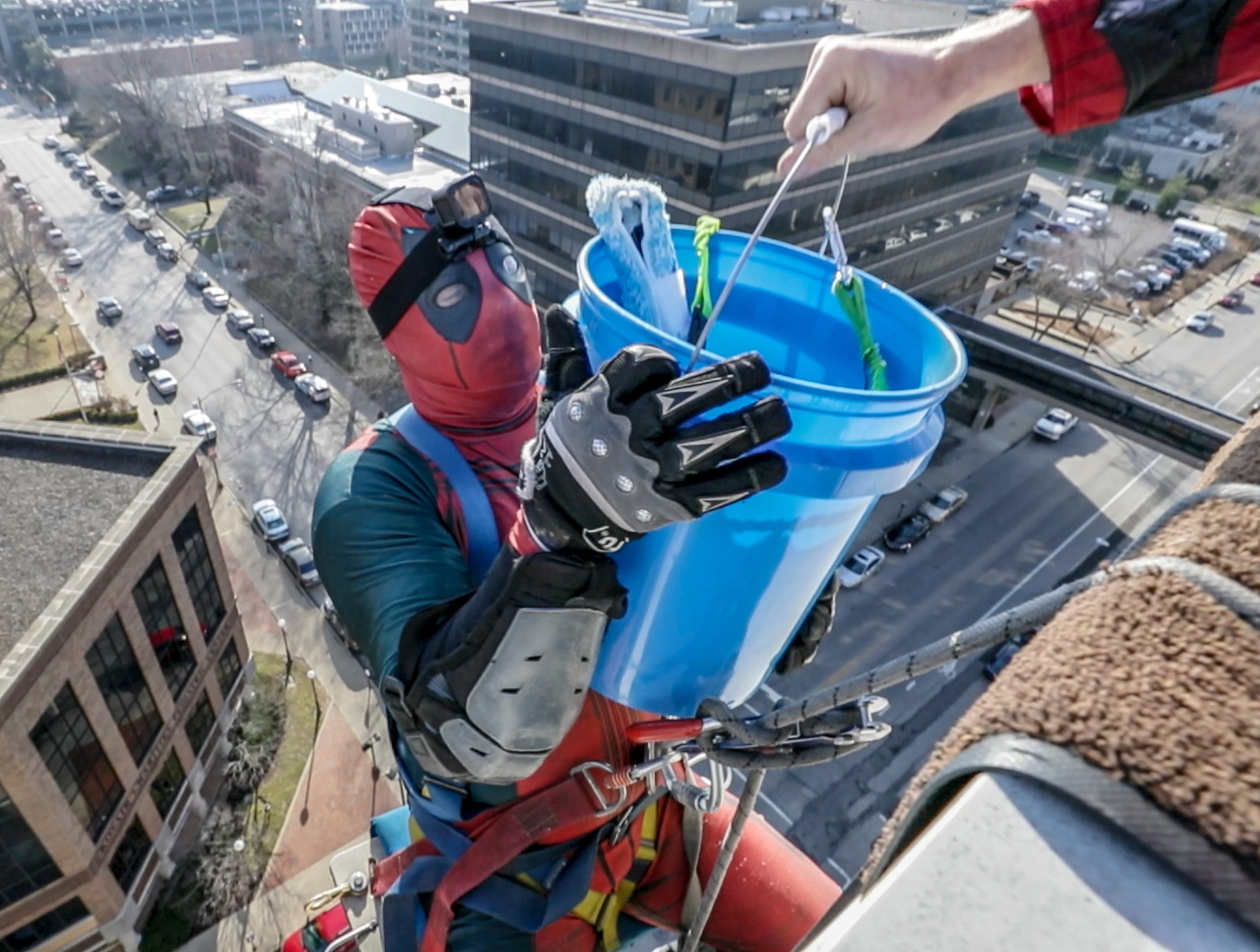 Window washer Johnny Haist, with Pro Clean International, portraying Deadpool, is handed a bucket of window cleaning solution as he prepares to descend from the roof of Norton Children's Hospital on Thursday morning.February 21, 2019