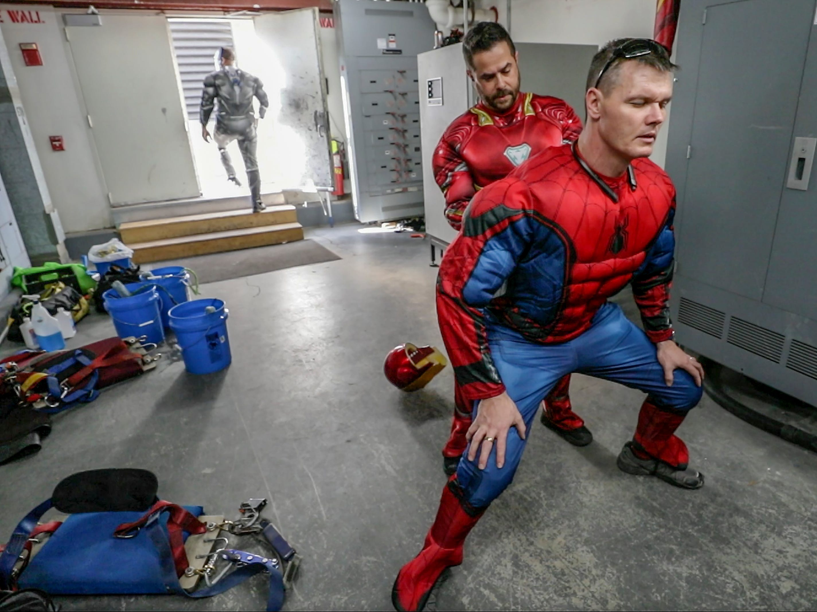 Window washer Joe Haist, with Pro Clean International, portraying Iron Man, helps Lonnie Hart put on his costume before going over the roof of Norton Children's Hospital on Thursday morning.February 21, 2019