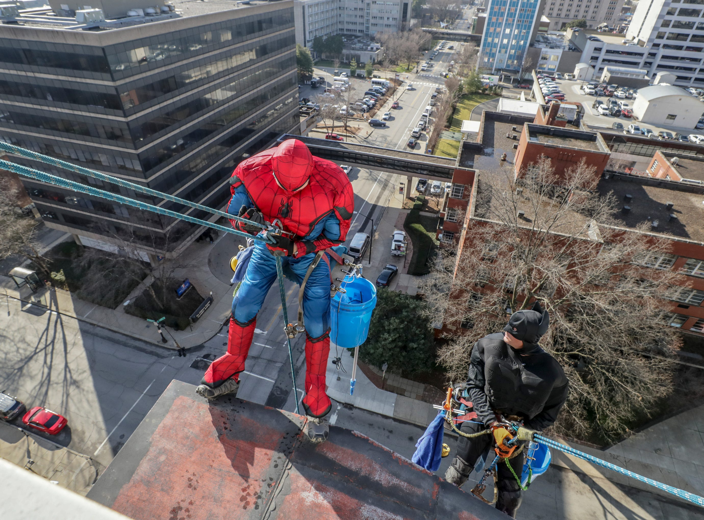 Window washer Lonnie Hart, with Pro Clean International, portraying Spider-Man, descends from the roof of Norton Children's Hospital on Thursday morning.February 21, 2019