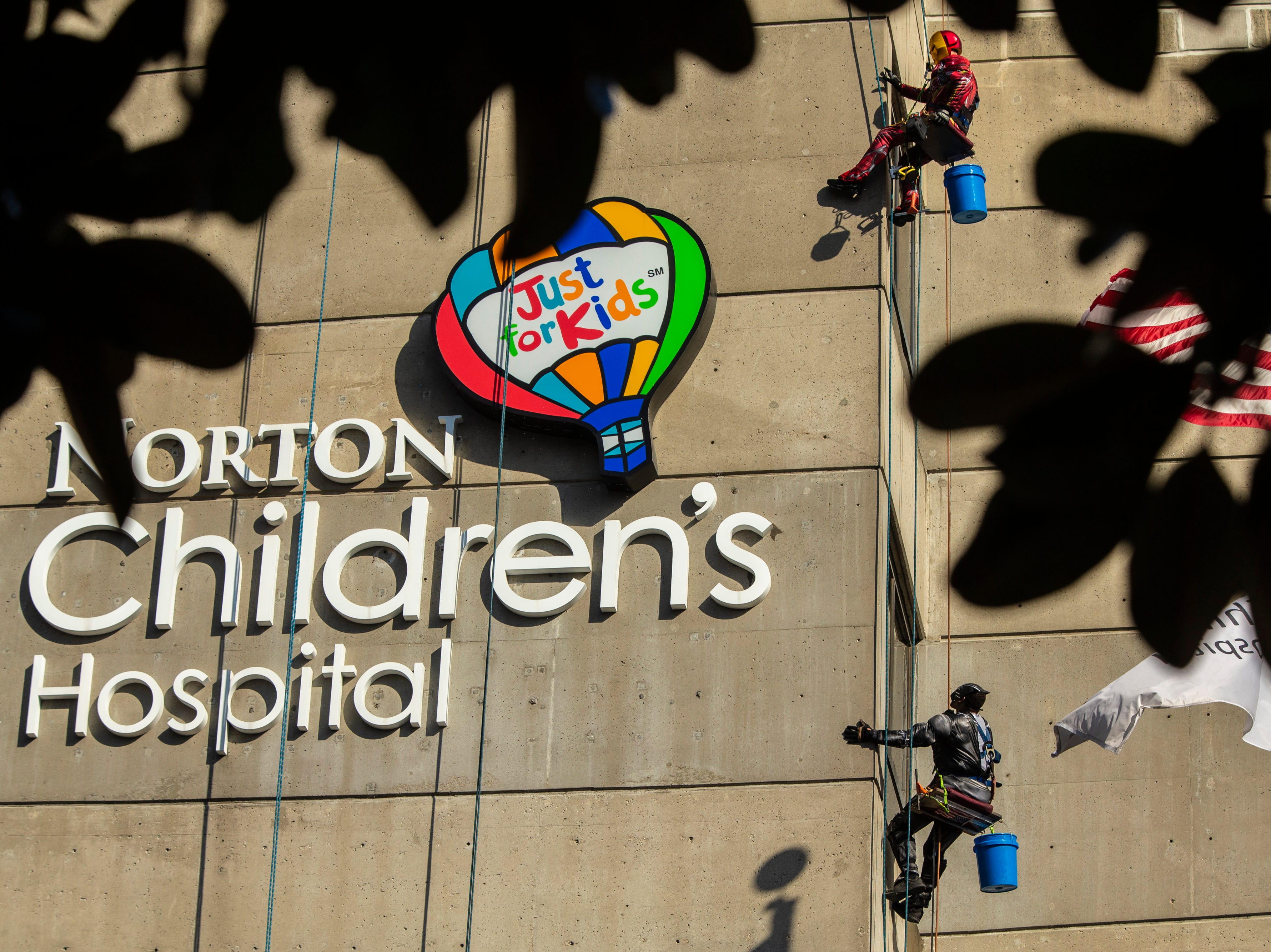 Joe Haist, top, and Lionel Bass, with Pro Clean International, wear super hero costumes while cleaning the windows at Norton Children's Hospital on Thursday. Feb. 21, 2019