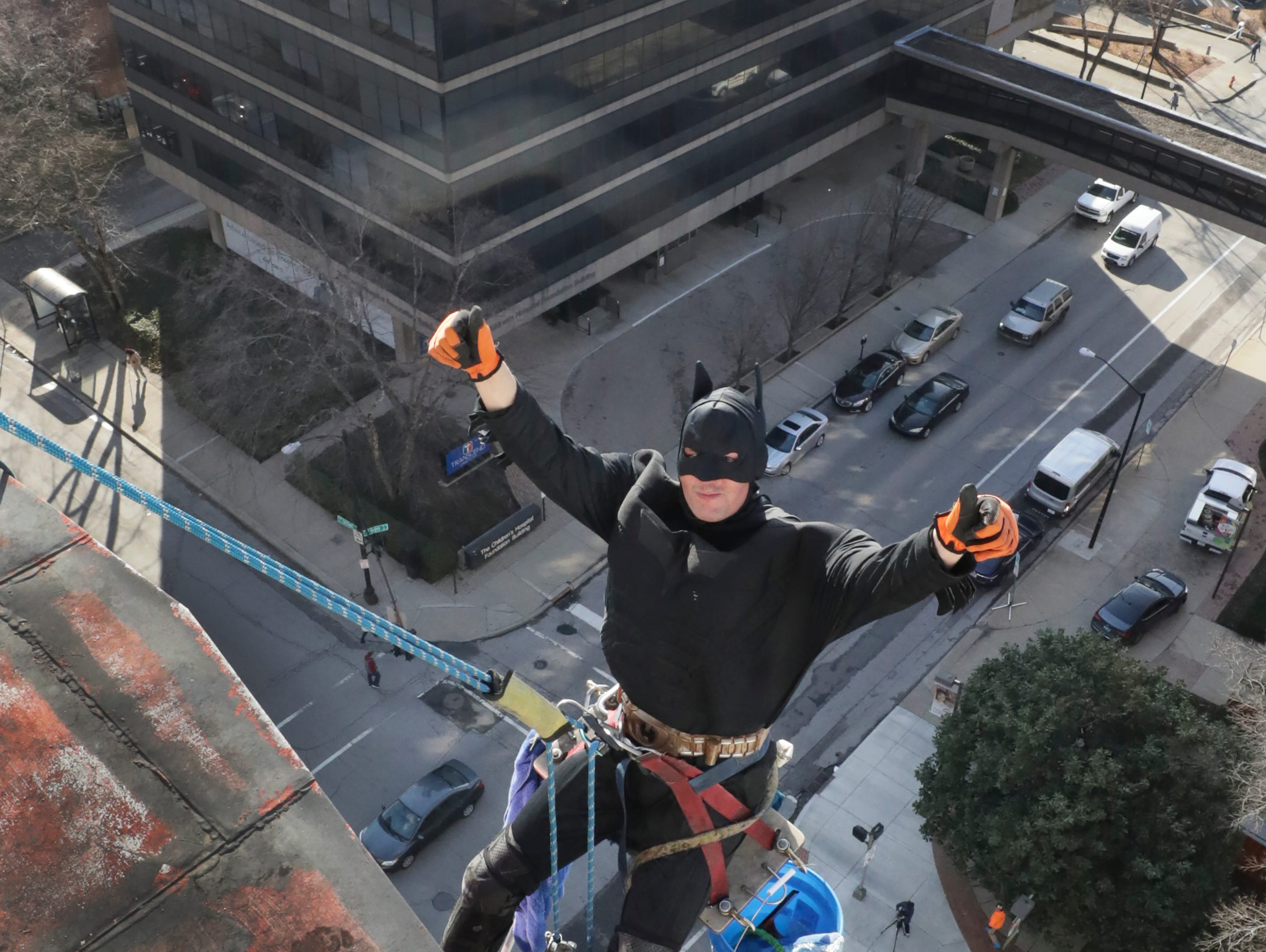 Window washer William Hart, with Pro Clean International, portraying Batman, descends from the roof of Norton Children's Hospital on Thursday morning.February 21, 2019