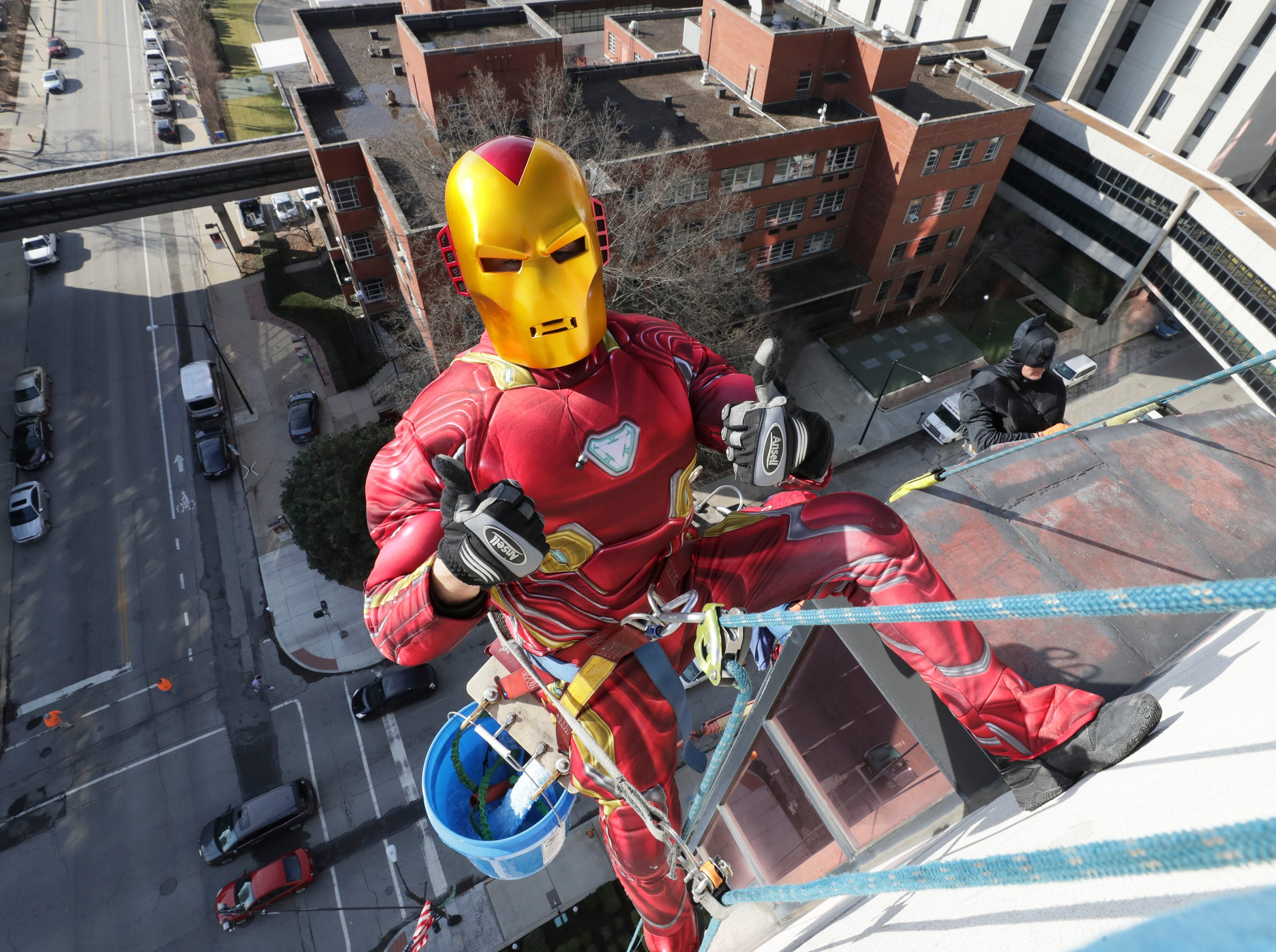 Window washer Joe Haist, with Pro Clean International, portraying Iron Man, descends from the roof of Norton Children's Hospital on Thursday morning.February 21, 2019