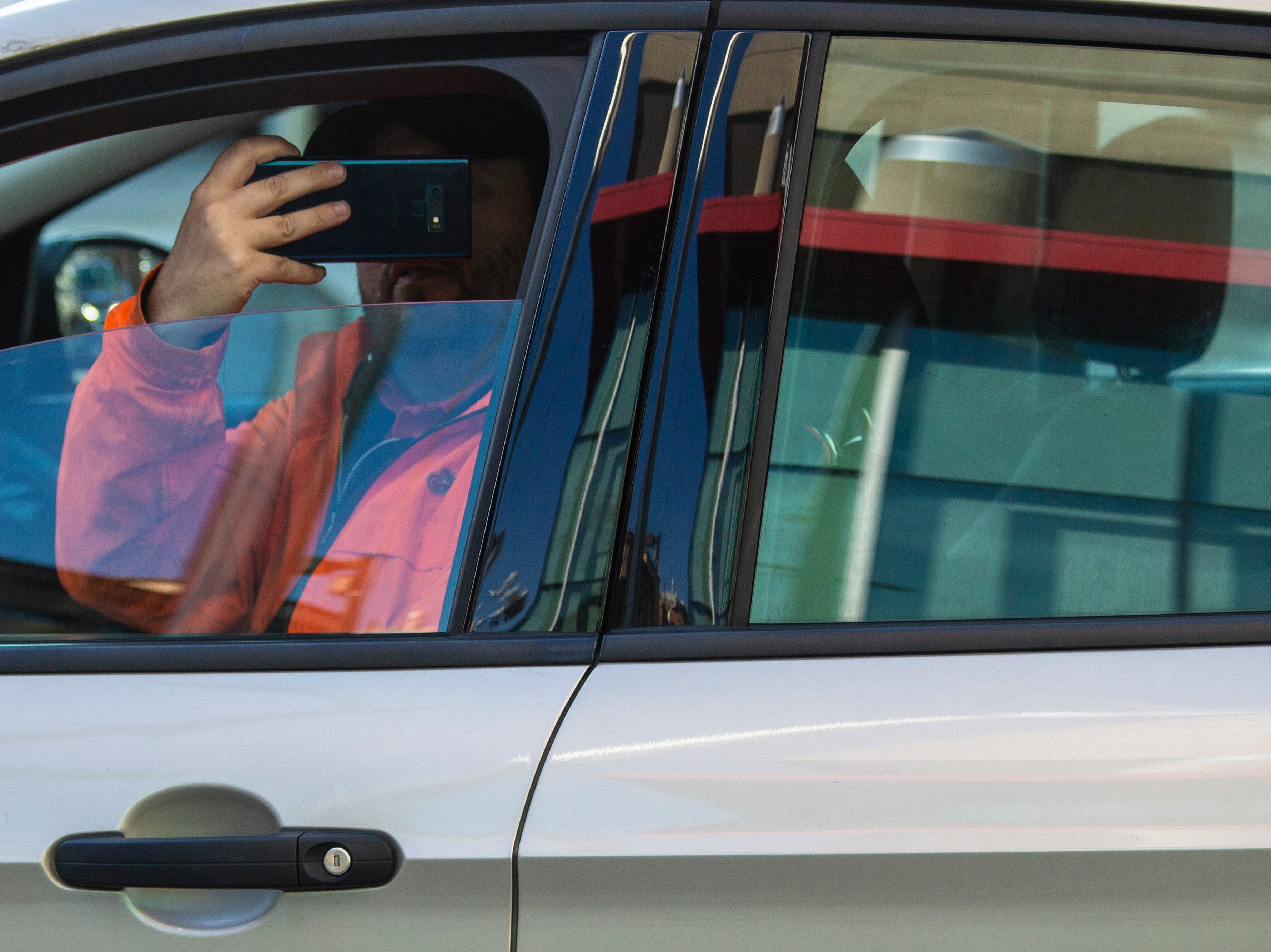 A motorist takes pictures of the Pro Clean International team wearing super hero costumes while cleaning the windows at Norton Children's Hospital on Thursday. Feb. 21, 2019