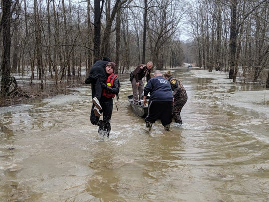 Four people were rescued after getting stranded for about 14 hours on top of their Jeep that got stuck in floodwaters near Maumee in Jackson County, Indiana.