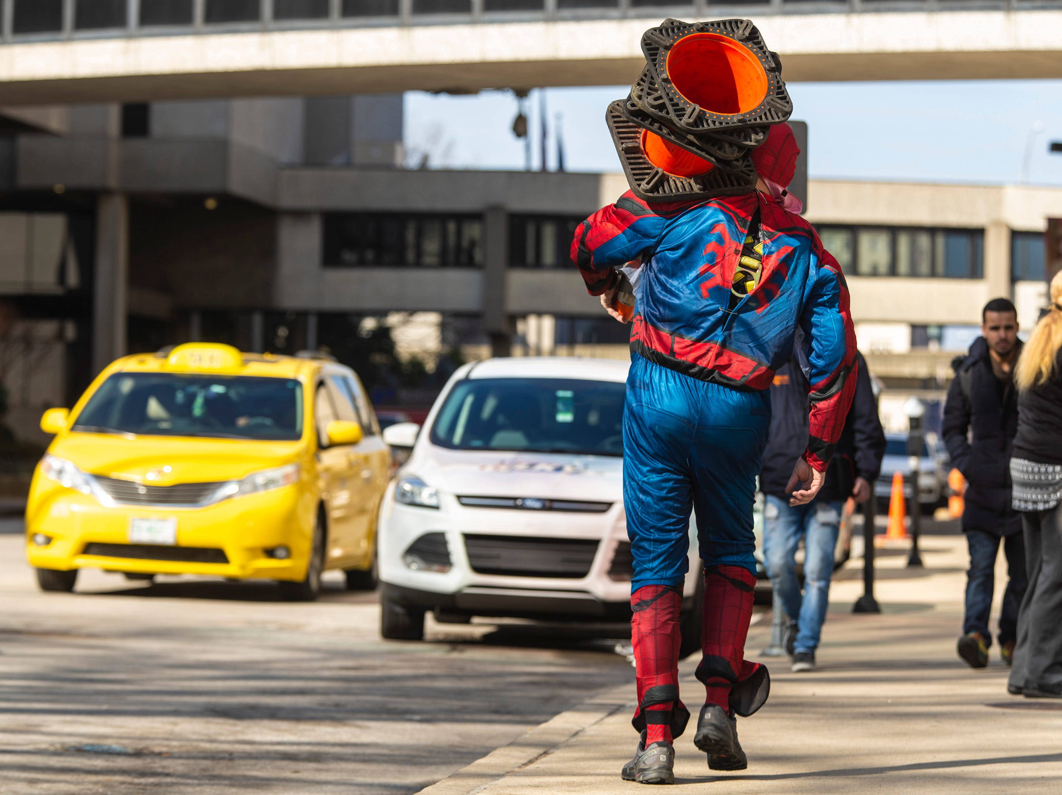 Duke Hart, with Pro Clean International, carries cones as the team wore super hero costumes while cleaning the windows at Norton Children's Hospital on Thursday. Feb. 21, 2019