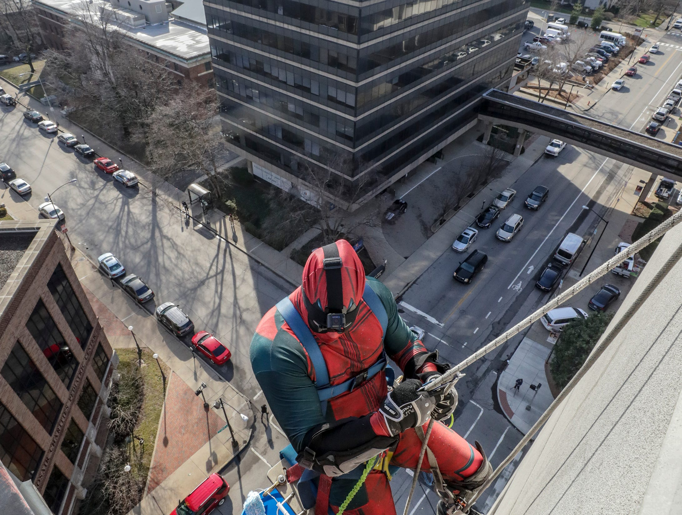 Window washer Johnny Haist, with Pro Clean International, portraying Deadpool, descends from the roof of Norton Children's Hospital on Thursday morning.February 21, 2019