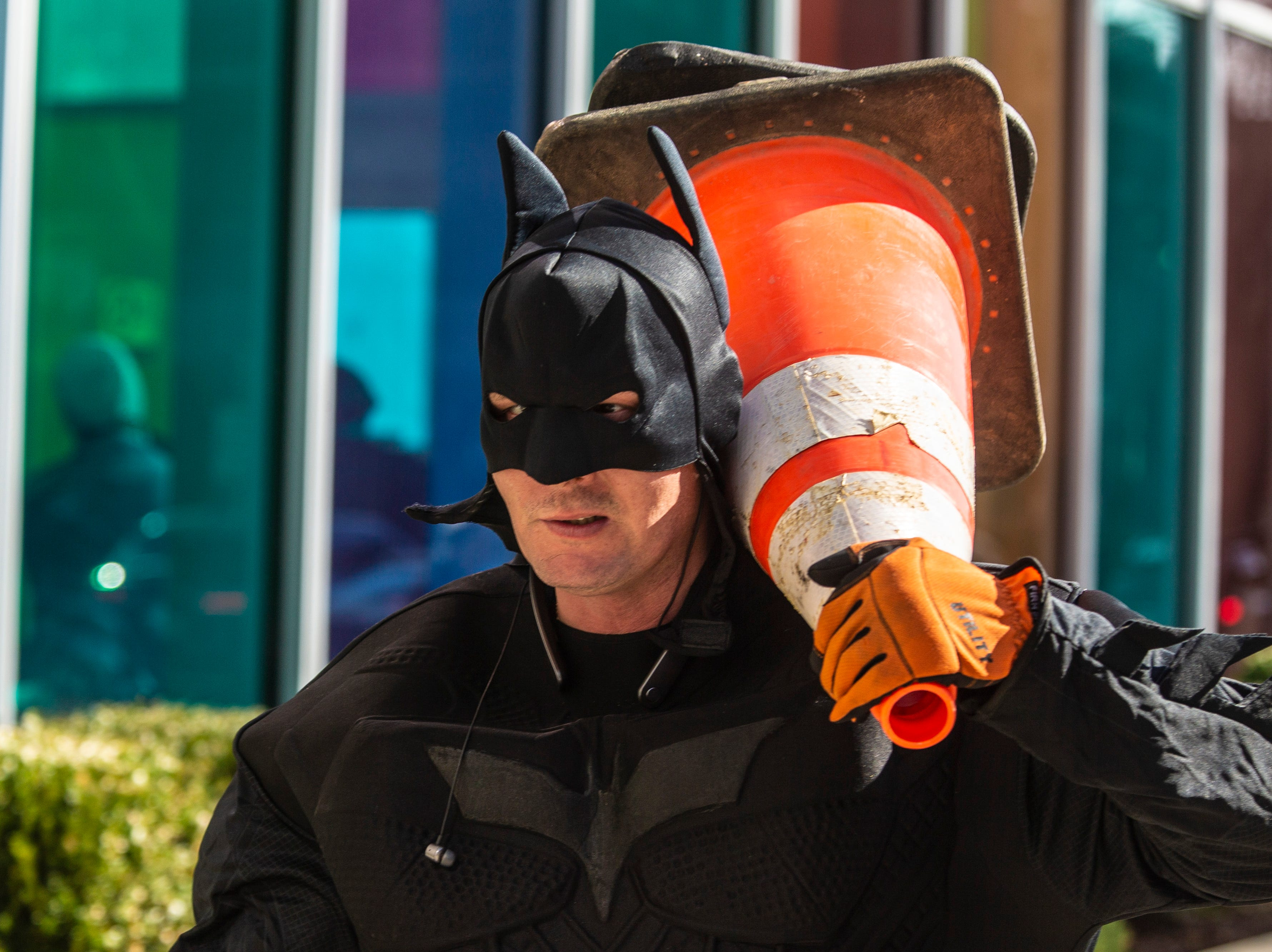 William Hart moves safety cones with Pro Clean International as the team wore super hero costumes while cleaning the windows at Norton Children's Hospital on Thursday. Feb. 21, 2019