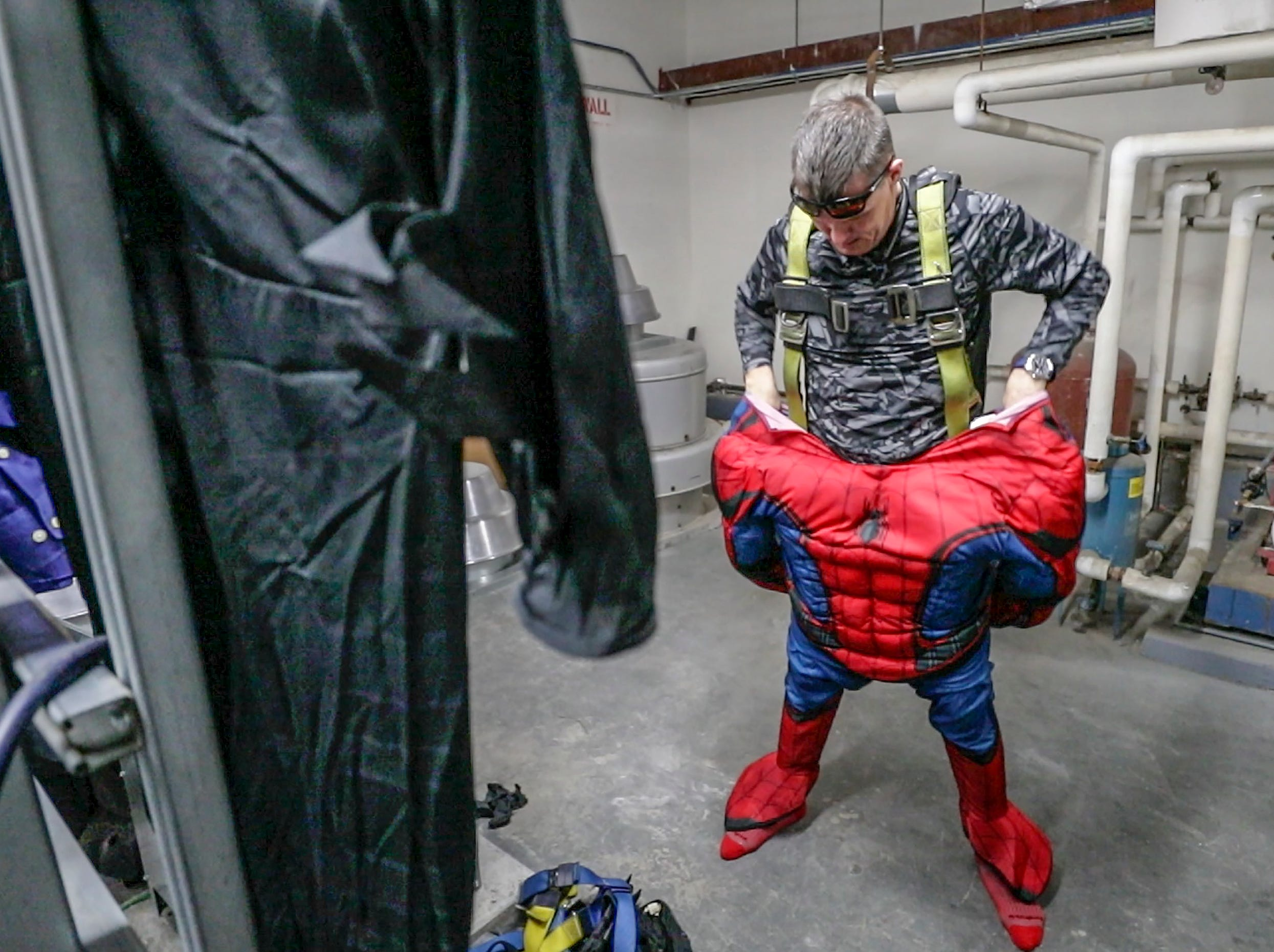 Window washer Lonnie Hart, with Pro Clean International, portraying Spider-Man, puts on his costume before going over the roof of Norton Children's Hospital on Thursday morning.February 21, 2019