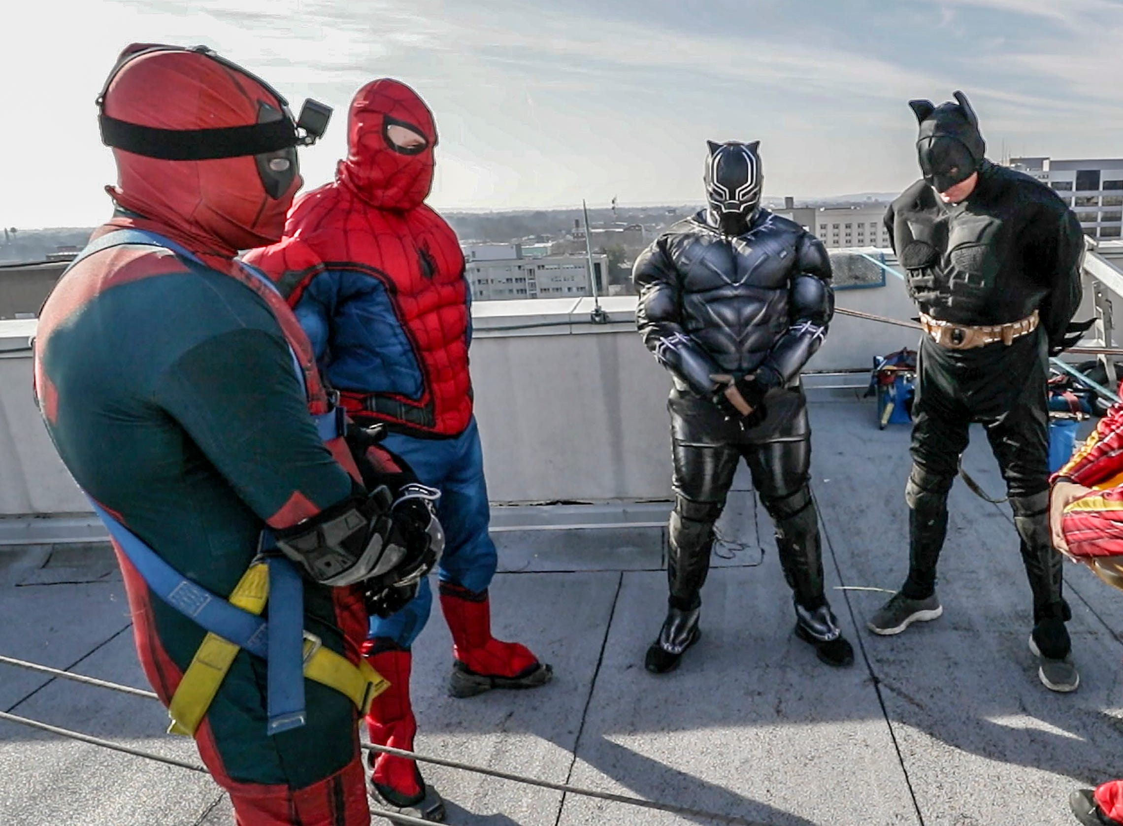 The group of window washers with Pro Clean International, prays before going over the roof at Norton Children's Hospital on Thursday morning.February 21, 2019