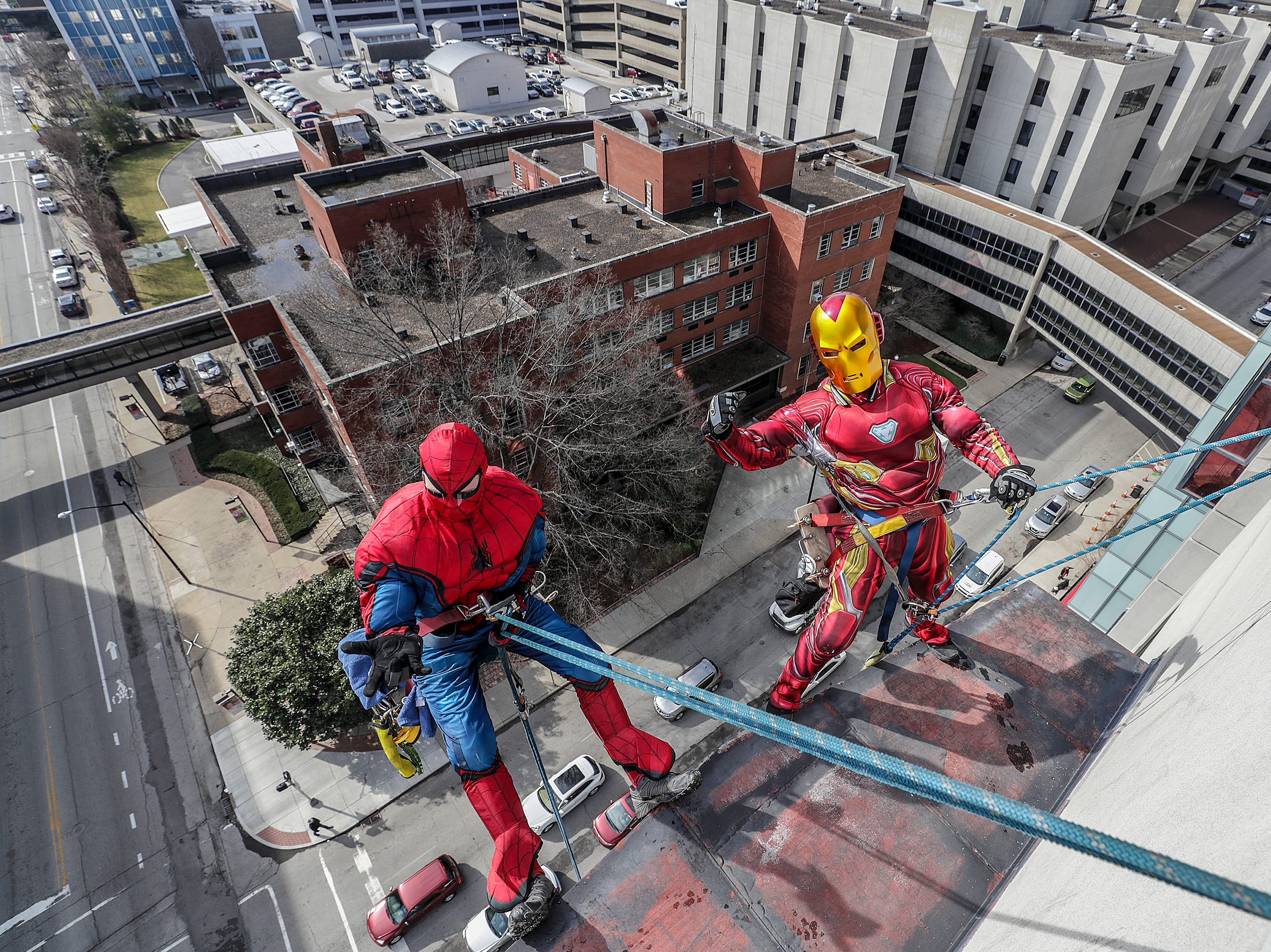 Window washers Lonnie Hart and Joe Haist, with Pro Clean International, portraying Spider-Man and Iron Man, descend from the roof of Norton Children's Hospital on Thursday morning.February 21, 2019