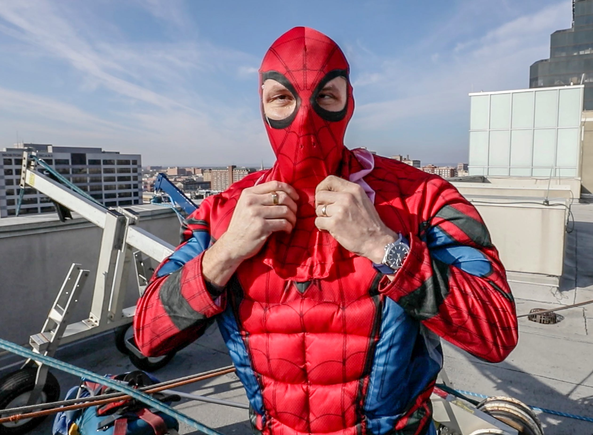 Window washer Lonnie Hart, with Pro Clean International, portraying Spider-Man, prepares to descend from the roof of Norton Children's Hospital on Thursday morning.February 21, 2019