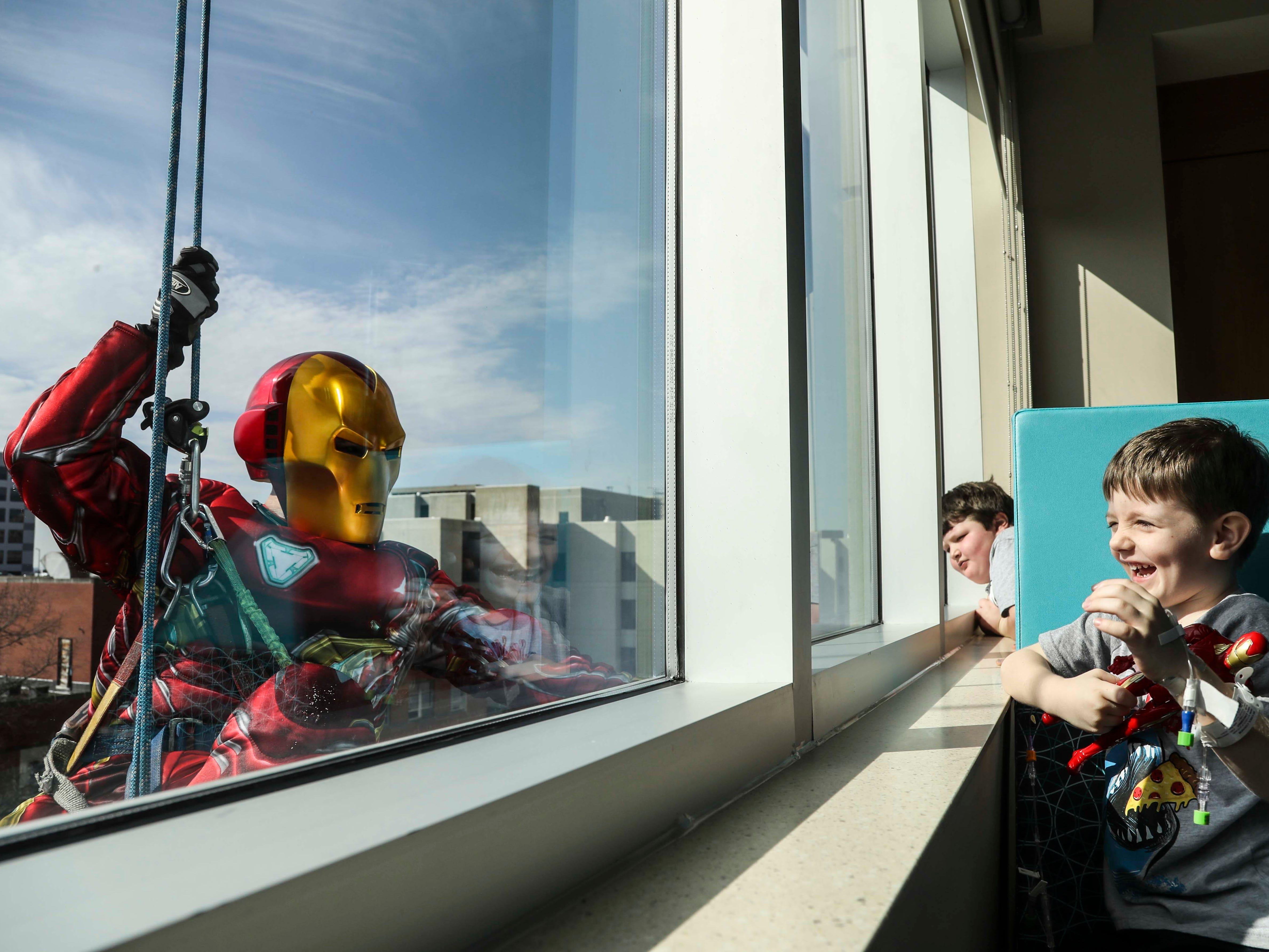 Connor Hughes, 5, laughs as Iron Man -- Joe Haist -- hangs outside a window at Norton Children's Hospital Thursday Feb. 21 2019.