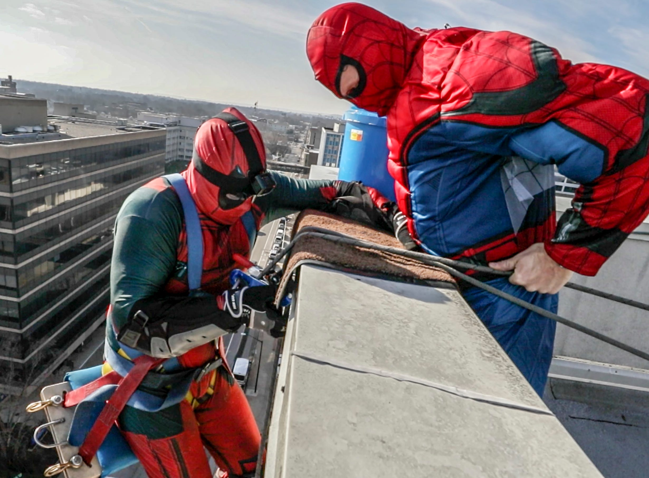 Window washers Johnny Haist and Lonnie Hart, with Pro Clean International, portraying Spider-Man and Deadpool, prepare to descend from the roof of Norton Children's Hospital on Thursday morning.February 21, 2019