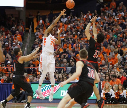 Syracuse's Tyus Battle, center, passes the ball over Louisville's Jordan Nwora, right, to break the press during the second half of an NCAA college basketball game in Syracuse, N.Y., Wednesday, Feb. 20, 2019. Syracuse won 69-49.