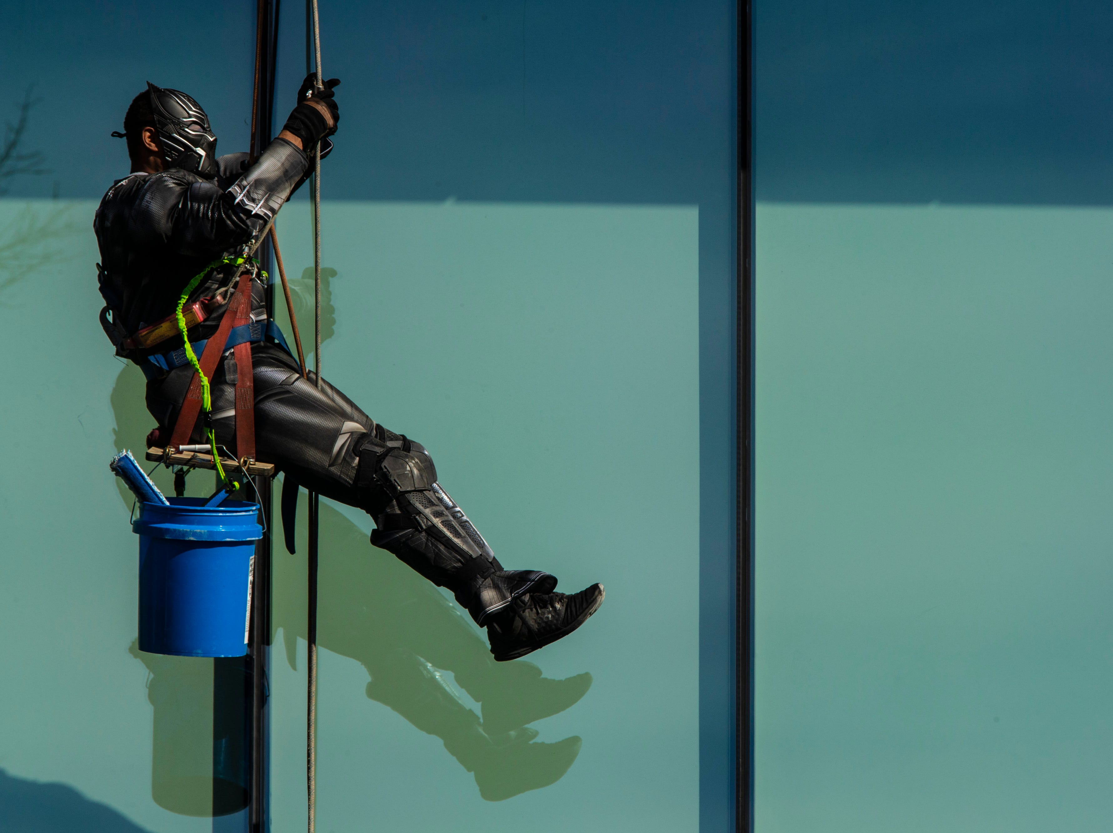 Lionel Bass with Pro Clean International wears a Black Panther costume as the team wore super hero costumes while cleaning the windows at Norton Children's Hospital on Thursday. Feb. 21, 2019