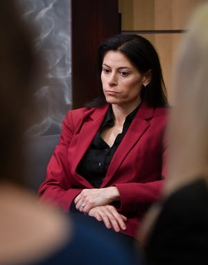 Michigan Attorney General Dana Nessel takes a seat after announcing that her office would investigate gymnastics coach John Geddert, Thursday, Feb. 21, 2019, during a press conference at the Frank Kelley Law Library at the AG's office.