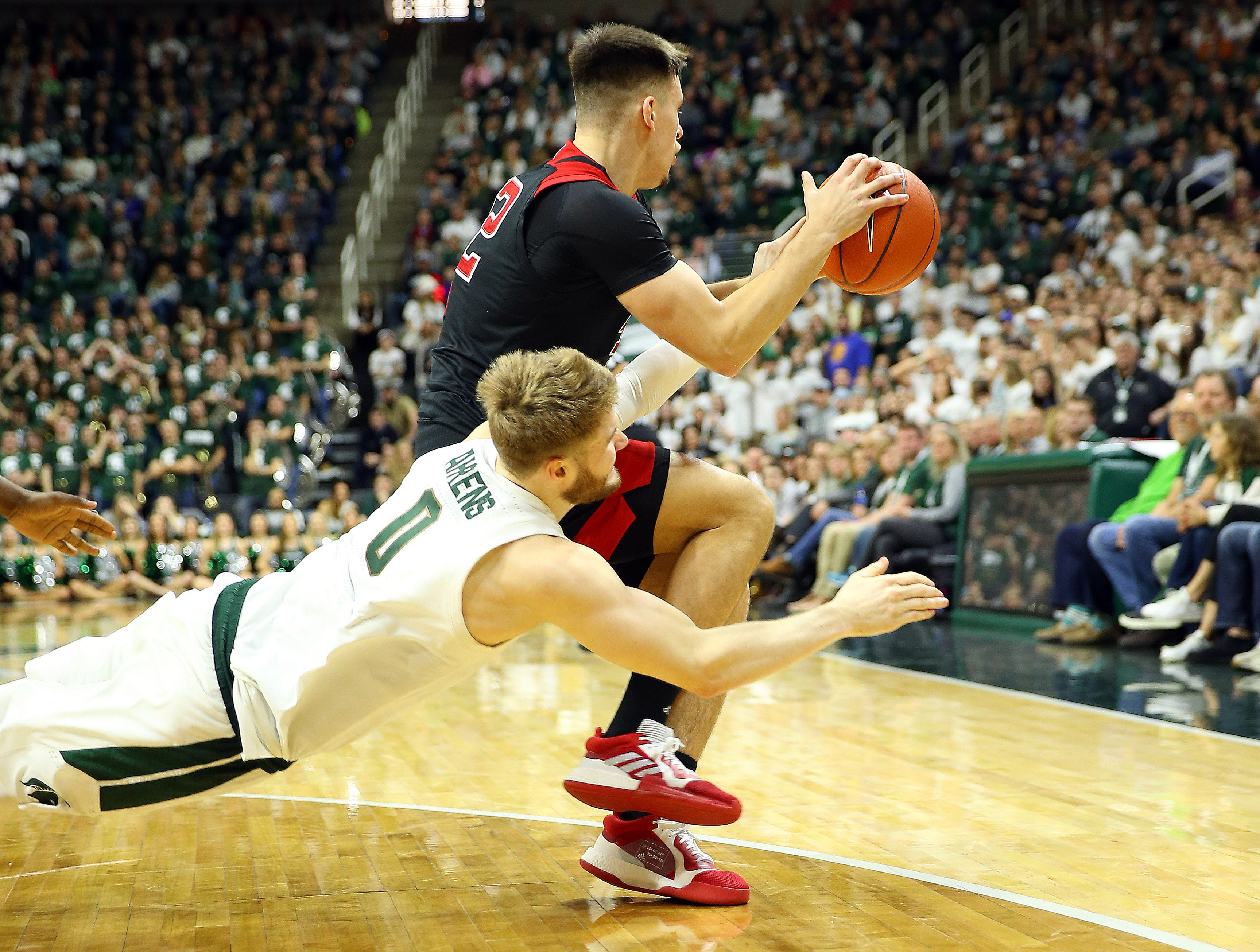 Feb 20, 2019; East Lansing, MI, USA; Michigan State Spartans forward Kyle Ahrens (0) dives after a loose ball against Rutgers Scarlet Knights center Shaquille Doorson (2) during the second half at the Breslin Center. Mandatory Credit: Mike Carter-USA TODAY Sports