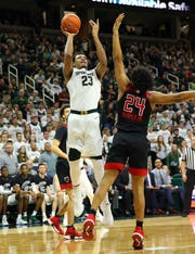 Feb 20, 2019; East Lansing, MI, USA; Michigan State Spartans forward Xavier Tillman (23) shoots the ball over Rutgers Scarlet Knights forward Ron Harper Jr. (24) during the second half of a game at the Breslin Center. Mandatory Credit: Mike Carter-USA TODAY Sports