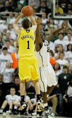 Michigan's Stu Douglass hits a long two-point shot over MSU's Draymond Green on Jan. 27, 2011.