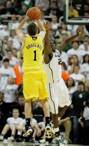 Michigan's Stu Douglass hits a long two-point shot over MSU's Draymond Green on Jan. 27, 2011.