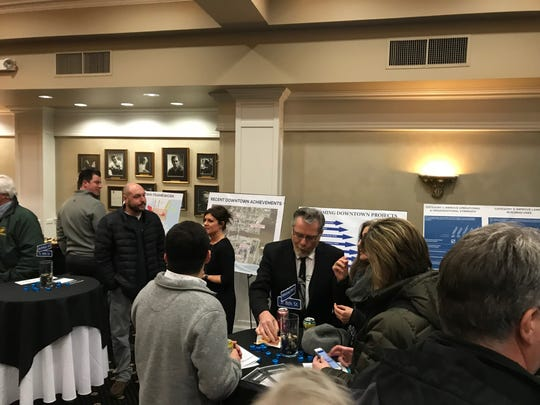 People gather and view signs detailing the Manitowoc Downtown Master Plan at the public information session Wednesday night at the Capitol Civic Centre.