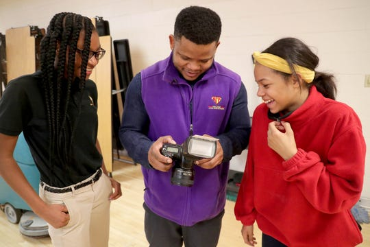 Milwaukee College Prep teacher Terrance Sims (center) looks at photos taken by sixth-grader Ryanne Rosemond (right) as fellow student Makynzie Russ  looks on.
