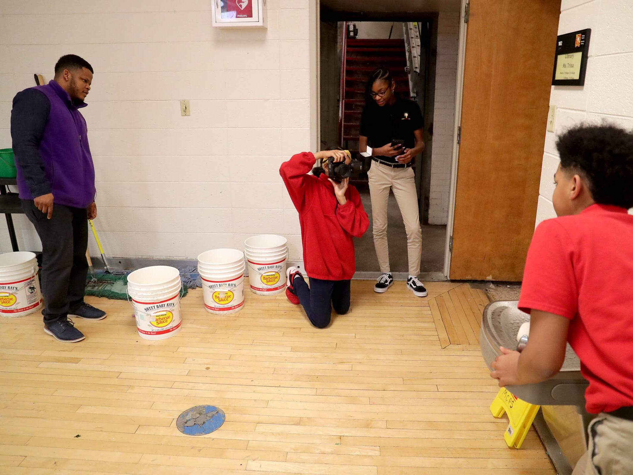 Milwaukee College Prep teacher Terrance Sims (left) and student Makynzie Russ (standing) watch as Ryanne Rosemond takes photos of Joey Hill reenacting a historic photo of Cecil Williams drinking from a whites-only water fountain in the 1950s.