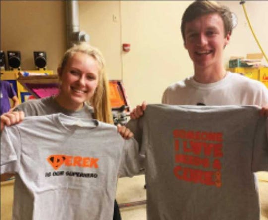 Two of Cathy Walz's graphic arts students, Madison Knitter (left) and Justin Krause (right) hold up T-shirts they made to help the Hilgemann family.