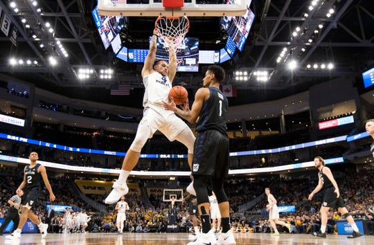 Marquette forward Thoe John hangs on the rim after a first-half dunk against Butler on Wednesday night.