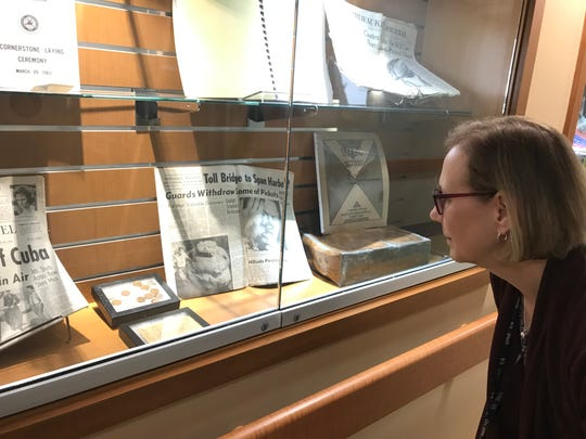 Janice Curnes, librarian at the Milwaukee VA Medical Center, looks at a display case featuring items put in a recently discovered time capsule. The time capsule was placed in a cornerstone of the hospital in 1963 during construction.