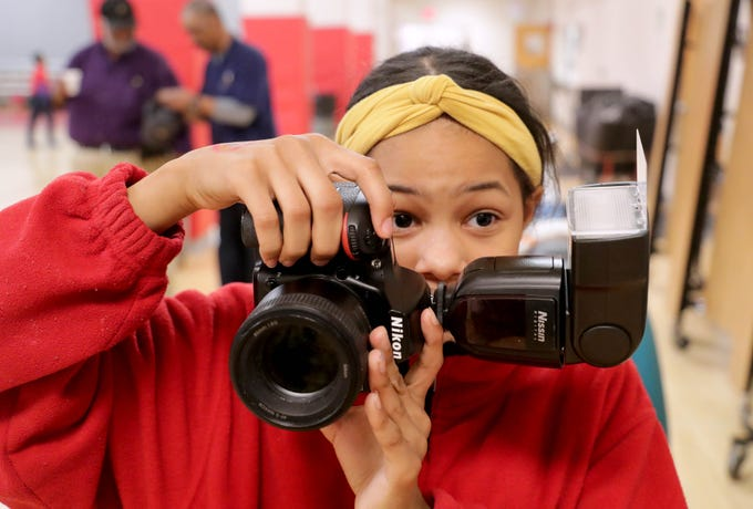 Ryanne Rosemond, a Milwaukee College Prep sixth-grader, takes photos as part of a school project in which students in teacher Terrance Sims' class re-create photos of famous and influential African-Americans for Black History Month.