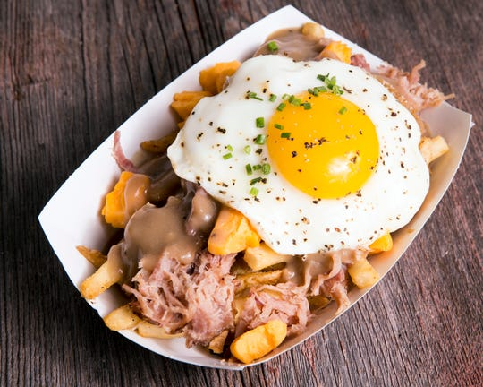 Loaded fries, like this poutine with pulled ham and a fried egg at Bass Bay Brewhouse, will be sold at Milk Can Hamburgers & Frozen Custard when it opens downtown.