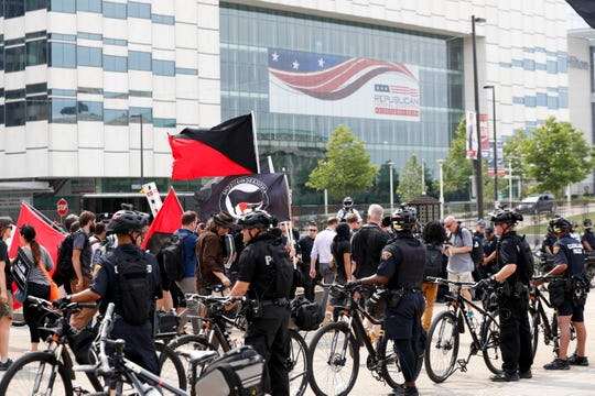 Protesters march as police look on near Public Square in Cleveland during the final day of the 2016 Republican convention.