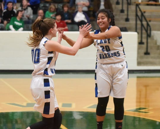 Cotter's Samantha Sanchez (20) and Kate Cheek (00) celebrate the Lady Warriors' victory over Mountainburg on Wednesday night.
