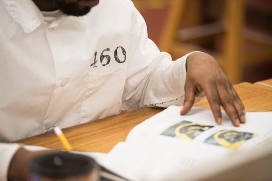 An inmate-student reads throw a book at the Ingram State Technical College Draper instructional service center in Elmore, Ala., on Thursday, Feb. 21, 2019.
