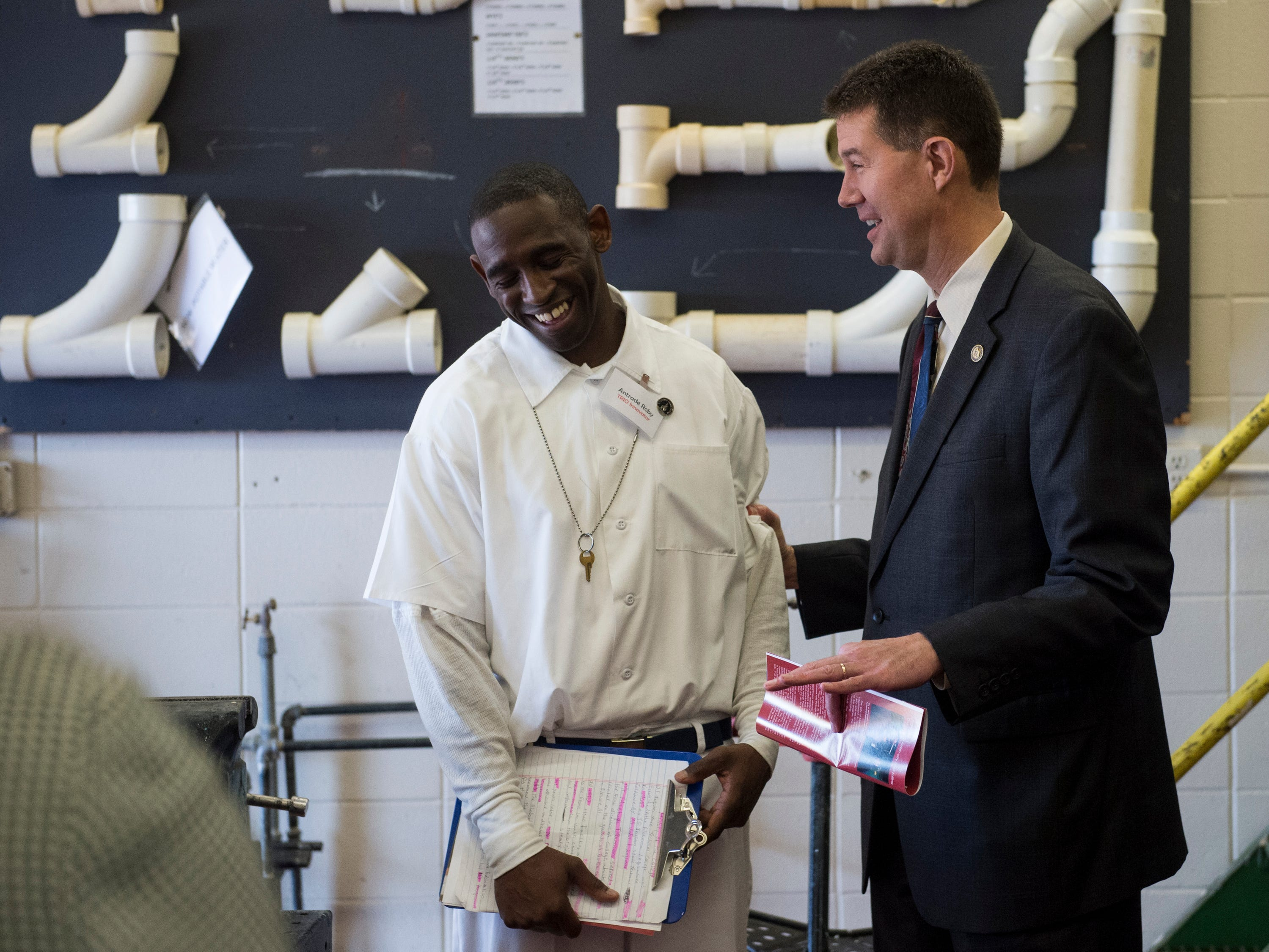 Student-inmate Antrade Roby and Alabama Secretary of State John Merrill joke during a tour at the Ingram State Technical College Draper instructional service center in Elmore, Ala., on Thursday, Feb. 21, 2019.