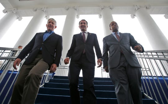 FILE - In this Jan. 12, 2018 file photo, Virginia Gov.-elect, Lt. Gov Ralph Northam, center, walks down the reviewing stand with Lt. Gov-elect, Justin Fairfax, right, and Attorney General Mark Herring at the Capitol in Richmond, Va.  The political crisis in Virginia exploded Wednesday, Feb. 6, 2019,  when the state's attorney general confessed to putting on blackface in the 1980s and a woman went public with detailed allegations of sexual assault against the lieutenant governor. With Northam's career already hanging by a thread over a racist photo, the day's developments threatened to take down all three of Virginia's top elected officials.  (AP Photo/Steve Helber, File)