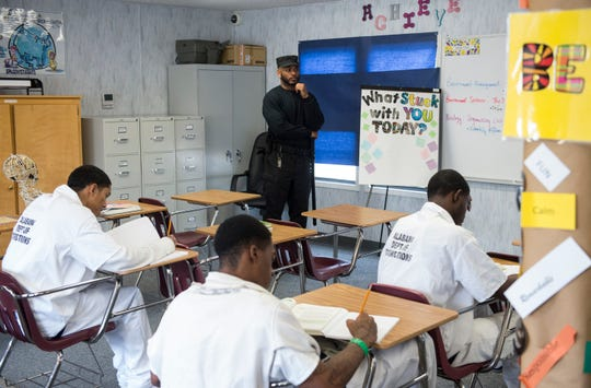 A correctional officer stands at attention in a science classroom for student-inmates at the Ingram State Technical College Draper instructional service center in Elmore, Ala., on Thursday, Feb. 21, 2019.