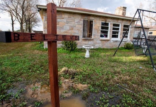 A cross that reads Believe stands in the front yard of the West family home in Montgomery, Ala., on Thursday February 21, 2019 after a house fire.
