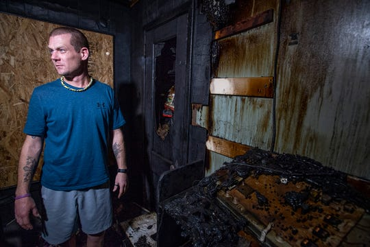 Justin West is gathering what is left of his families belongings, on Thursday February 21, 2019, after a house fire at their home in Montgomery, Ala.
