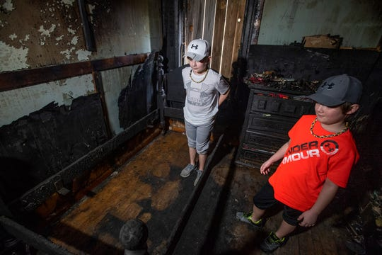 Kye West and his brother Reed check out their bedroom on Thursday February 21, 2019 as their family gathers what is left of their belongings after a house fire at their home in Montgomery, Ala. The fire apparently started under Kye's bed where he is standing.