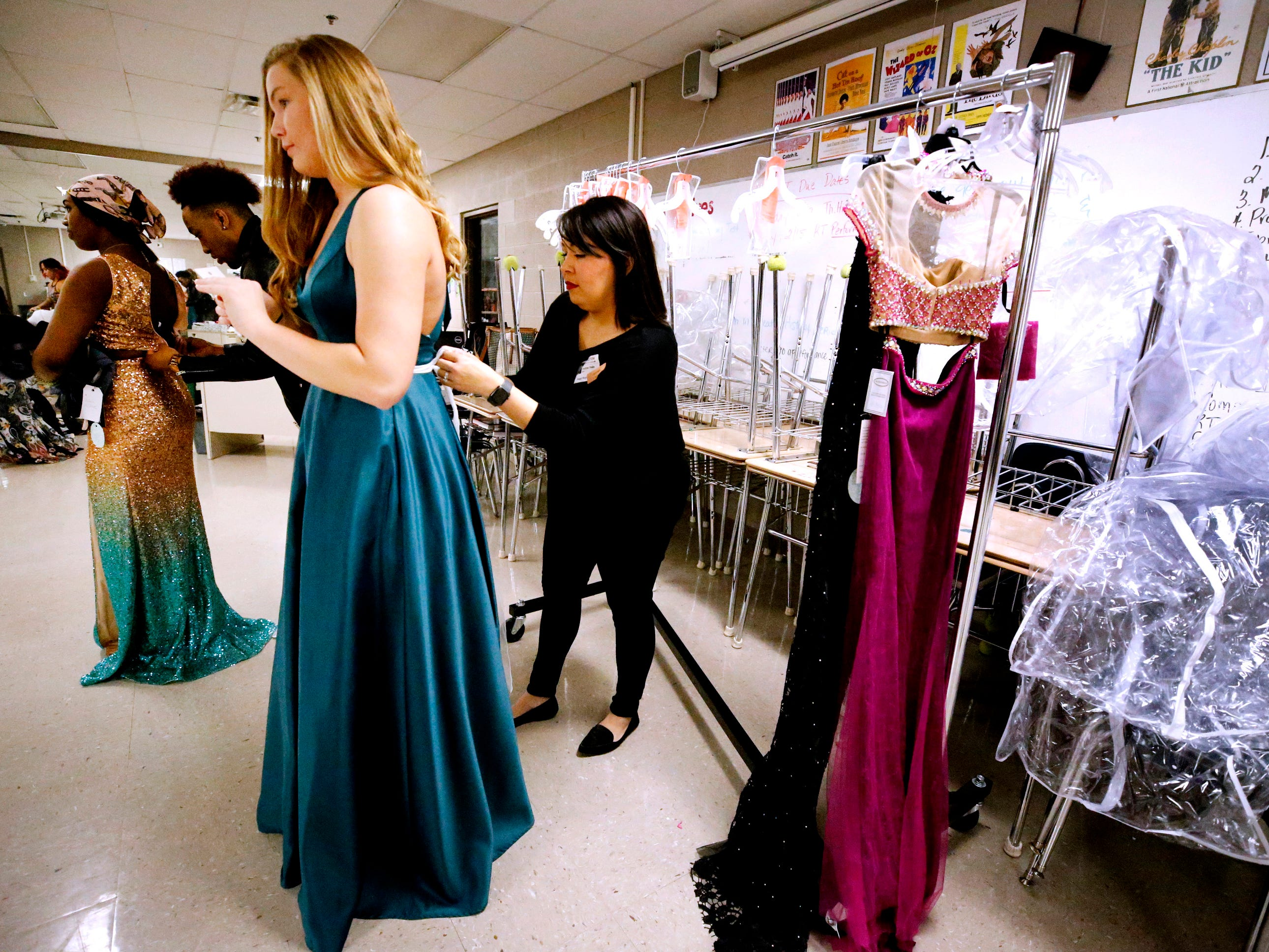 Heather Hale from David's Bridal ties a beaded sash onto Taylor Patterson's dress as they get ready for the Siegel Prom Fashion show on Thursday, Feb. 14, 2019.
