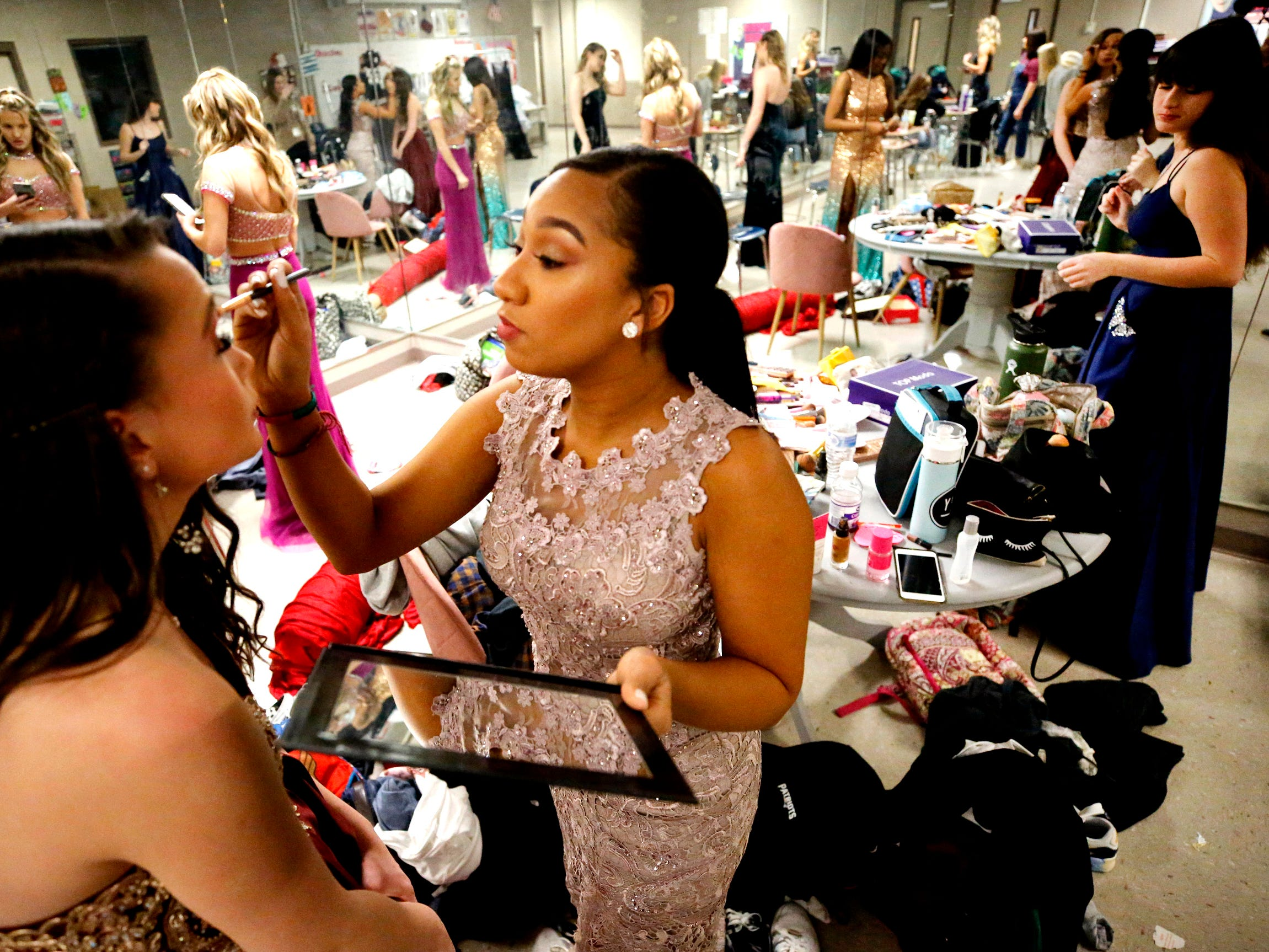 Aleah Carter, right, puts makeup on Jinni McCullough as the two get ready for the Siegel Prom Fashion Show on Feb. 14, 2019.