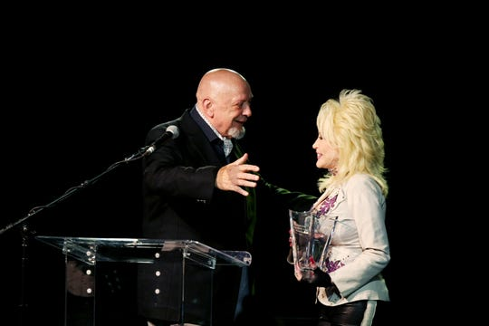 Fred Foster, left, is given an award by Dolly Parton during the Leadership Music Dale Franklin Award gala dinner in 2010. Foster helped launch Parton's career.