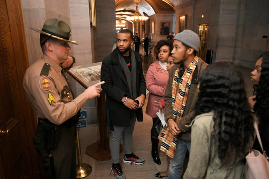 A Tennessee Highway Patrol officer speaks to protesters after they confronted Speaker of the House Glen Casada before a press conference on healthcare Thursday, Feb. 21, 2019, at the Capital in Nashville, Tenn.
