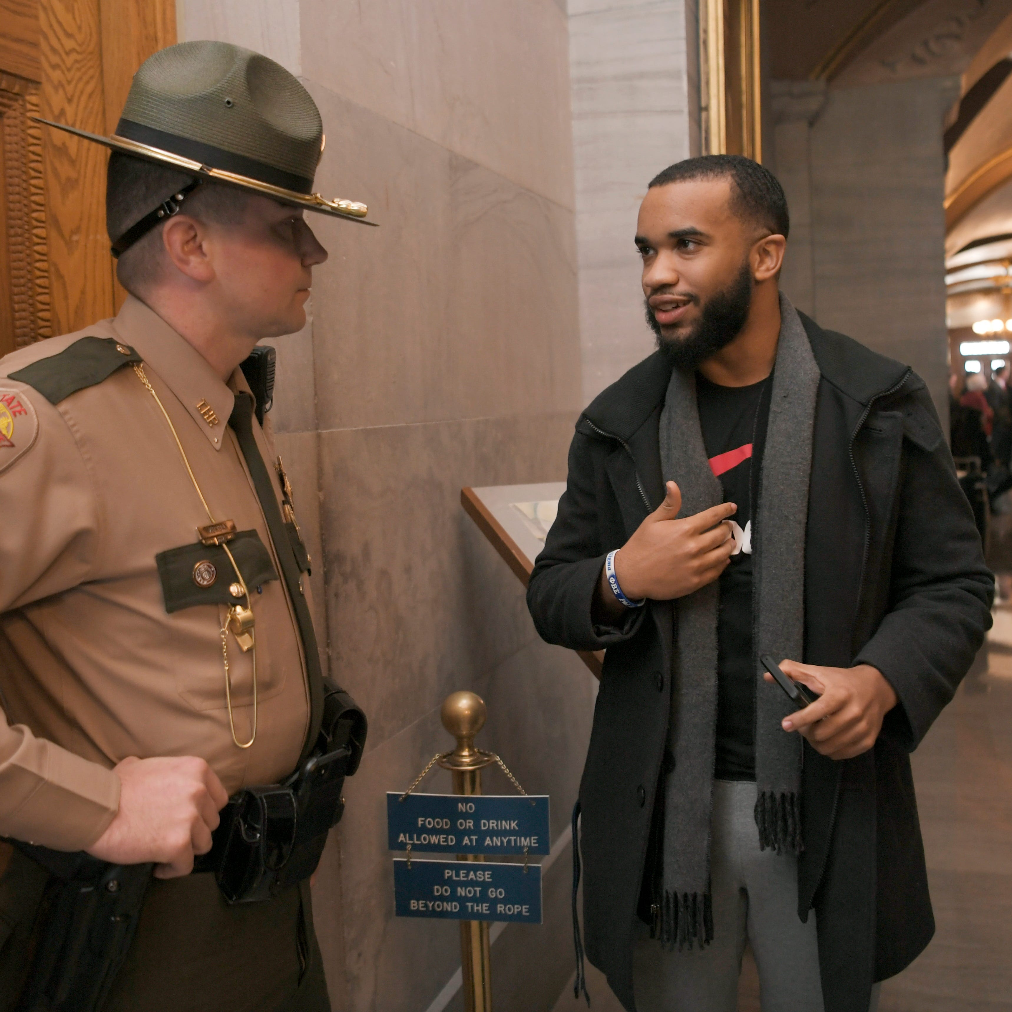 A Tennessee Highway Patrol officer speaks to a protester after a group confronted Speaker of the House Glen Casada before a press conference on healthcare Thursday, Feb. 21, 2019, at the Capitol in Nashville, Tenn.