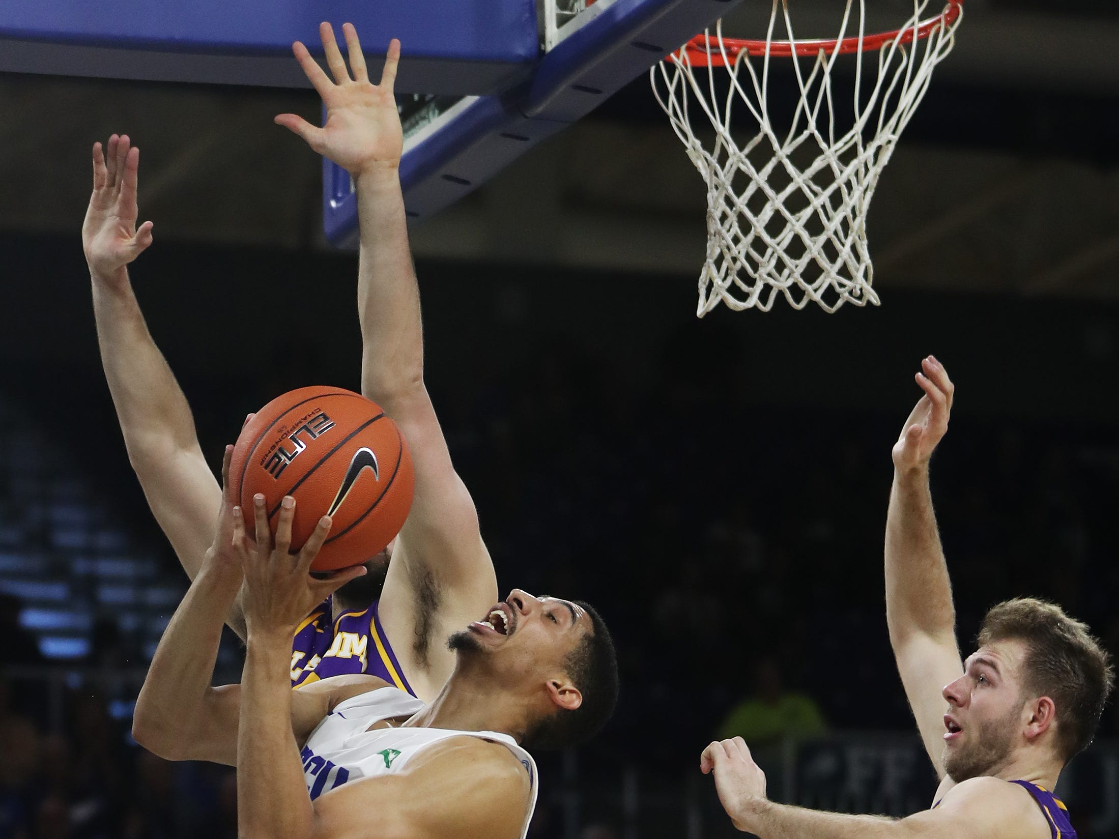 Florida Gulf Coast University's Dinero Mercurius drives to the basket against Lipscomb's Matt Rose on Wednesday at FGCU in Fort Myers. FGCU beat Lipscomb 67-61.