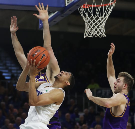 FGCU's Dinero Mercurius drives to the basket against Lipscomb's Matt Rose on Wednesday at FGCU in Fort Myers. FGCU beat Lipscomb 67-61.